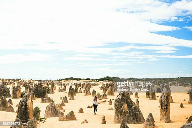 Woman Standing By Limestones At Nambung National Park Against Sky