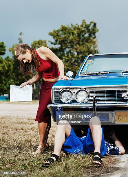 woman standing by man working underneath car, holding map - under skirt stock photos and pictures
