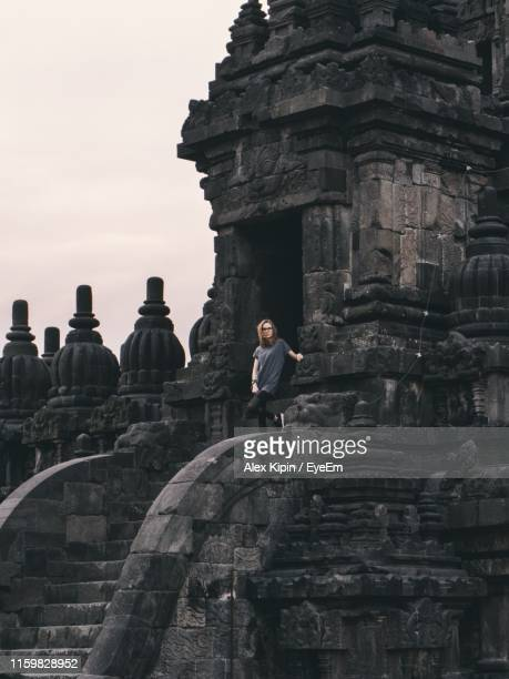 woman standing by old ancient temple - surabaya stock pictures, royalty-free photos & images