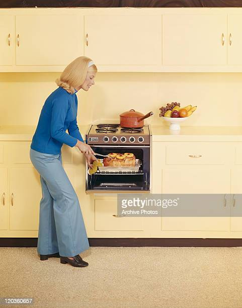 Woman standing by oven touching cake