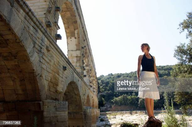 Woman Standing By Pont Du Gard Against Sky