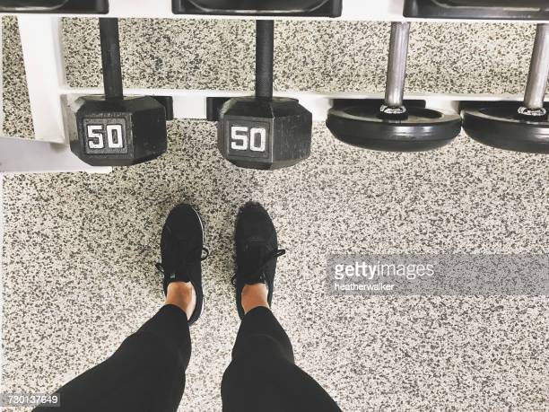 Woman standing by rack of dumbbells in gym