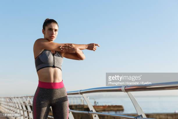 woman standing by railing against clear sky - crop top stock pictures, royalty-free photos & images