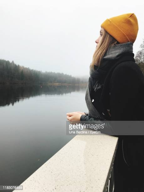 woman standing by railing against sky during winter - una persona stock pictures, royalty-free photos & images