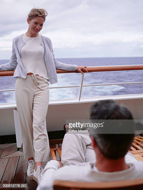 woman standing by railing, man sitting on deckchair on cruise ship - passenger craft stock pictures, royalty-free photos & images