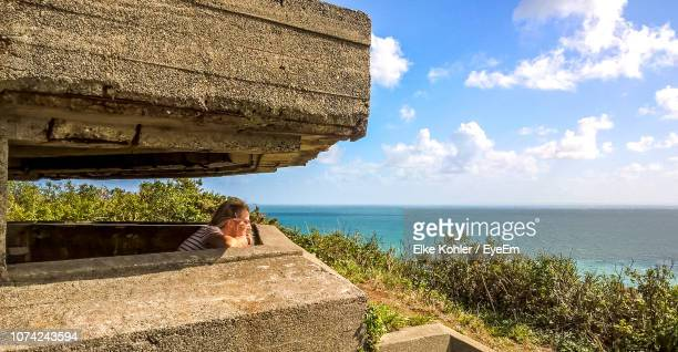 woman standing by retaining wall against sea - isola di guernsey foto e immagini stock