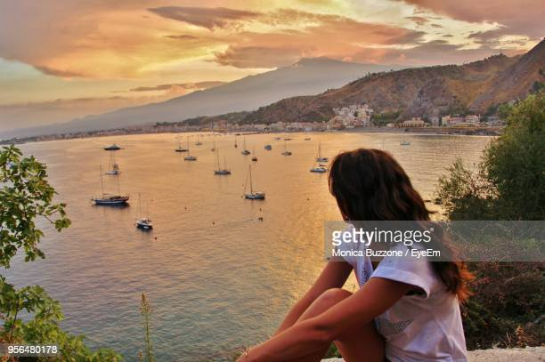 woman standing by sea against sky during sunset - taormina stock pictures, royalty-free photos & images