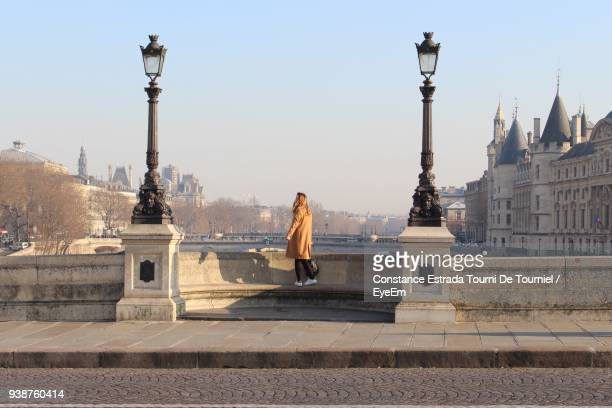 woman standing by sidewalk against clear sky - paris france photos et images de collection