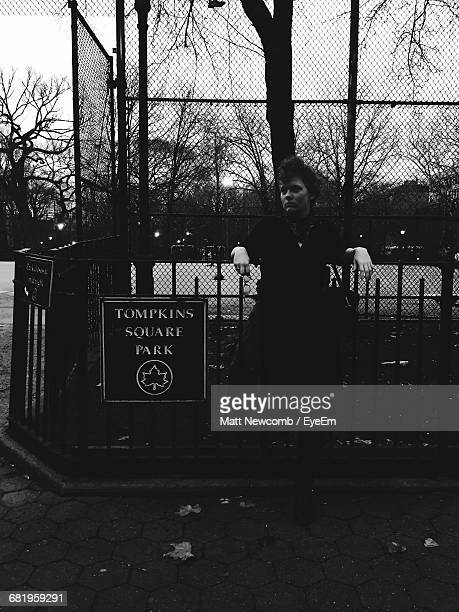 woman standing by sign on railing at tompkins square park - east village stock pictures, royalty-free photos & images