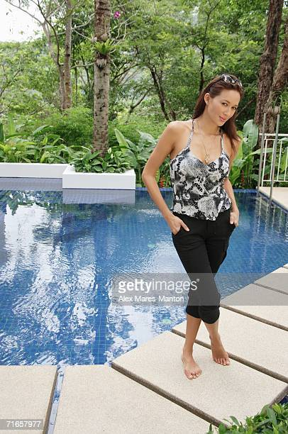 Woman standing by swimming pool, hands in pocket