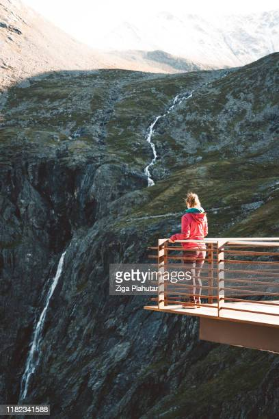 woman standing by the fence on viewpoint platform trollstigen - northern rail stock pictures, royalty-free photos & images
