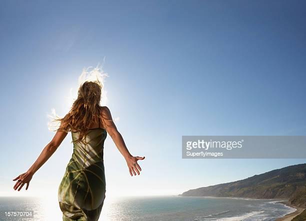 Mujer de pie por el mar con brazos estirados