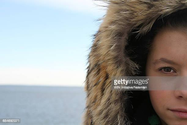 Woman standing by the sea in a fur hood