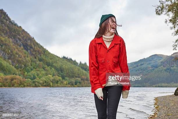 woman standing by the side of a loch - red coat stock pictures, royalty-free photos & images