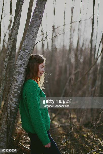 Woman standing by the tree