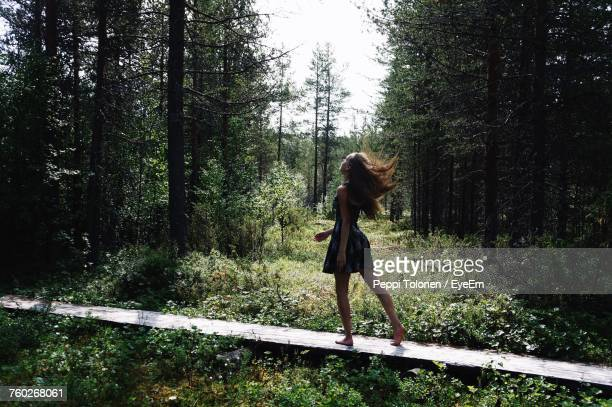 woman standing by tree in forest against sky - ragazzine scalze foto e immagini stock