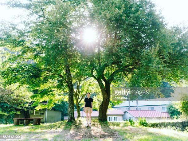 女性の木のそばに立って