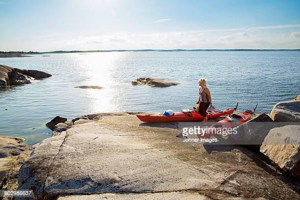 Woman standing by two kayaks on lakeshore