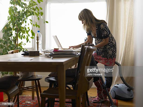 Woman standing by vacuum cleaner using laptop on dining table