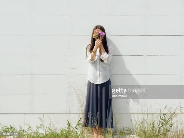 mulher em pé por parede cobrindo o rosto com flores - rosto coberto - fotografias e filmes do acervo