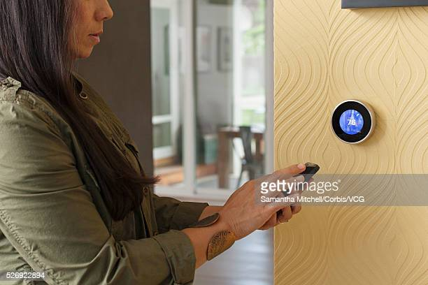 woman standing by wall with thermostat and using smart phone - thermostat stock photos and pictures