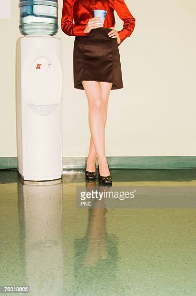 Woman standing by water cooler