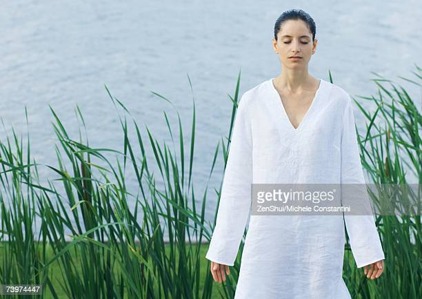 Woman standing by water, meditating