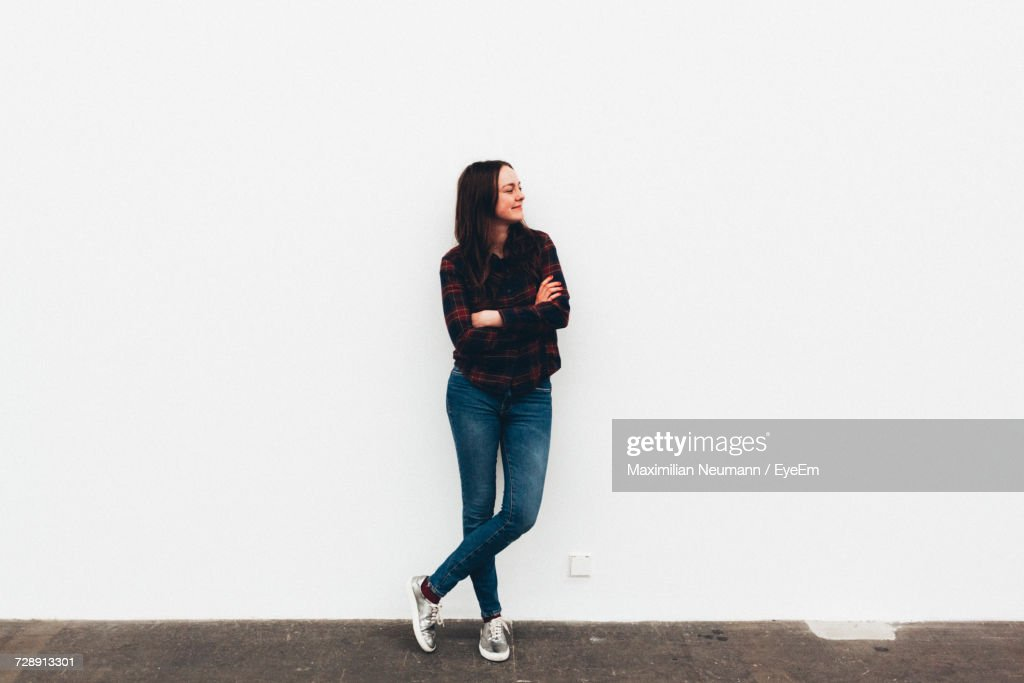 Woman Standing By White Wall : Photo