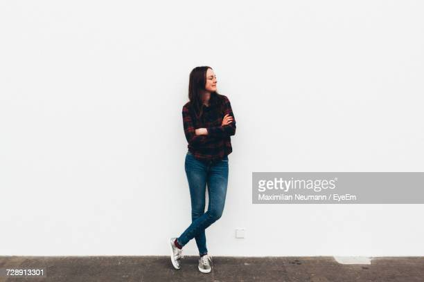 woman standing by white wall - stehen stock-fotos und bilder