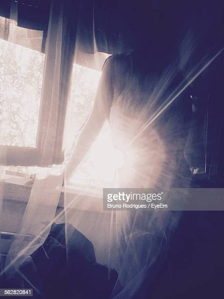 Woman Standing By Window At Sunny Day