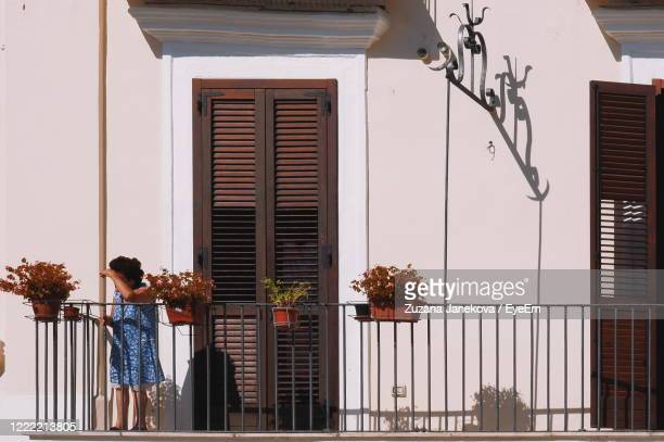 woman standing by window of building - zuzana janekova stock pictures, royalty-free photos & images