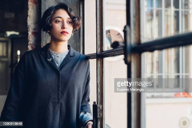 woman standing by window - endast en ung kvinna bildbanksfoton och bilder