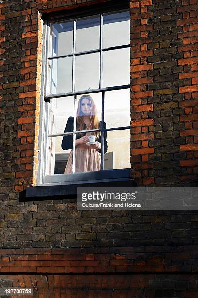 Woman standing by window with cup