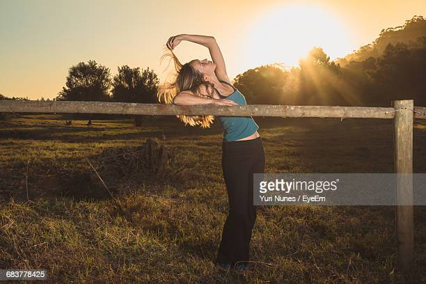 Woman Standing By Wooden Fence In Park