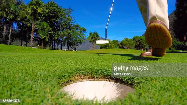 Woman Standing Close to the Golf Hole