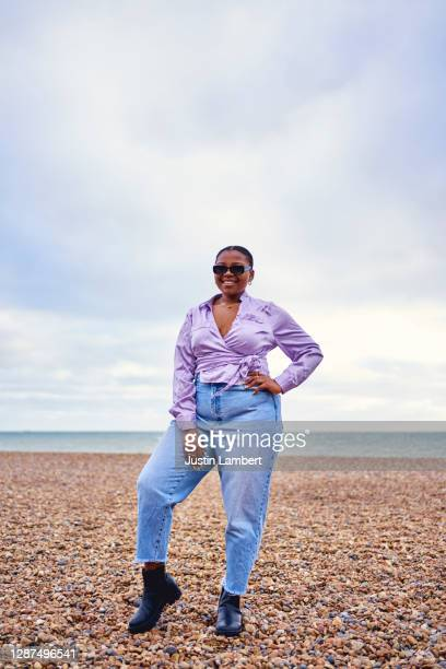 woman standing confidently posing alone at the beach wearing sunglasses - full length stock pictures, royalty-free photos & images