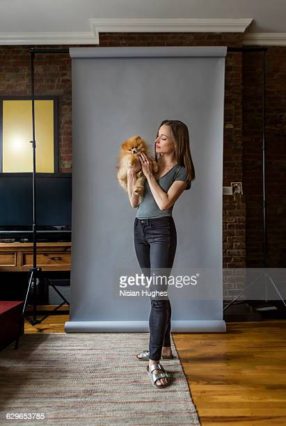 Woman standing holding pet dog