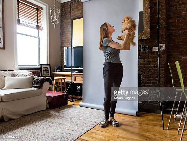 Woman standing holding up pet dog