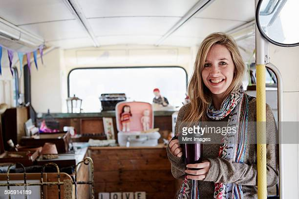 A woman standing in a bus converted into a vintage shop at a flea market surrounded by vintage objects.