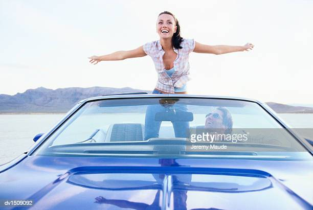 Woman Standing in a Convertible Car in a Desert With Her Arms Out and a Man Driving