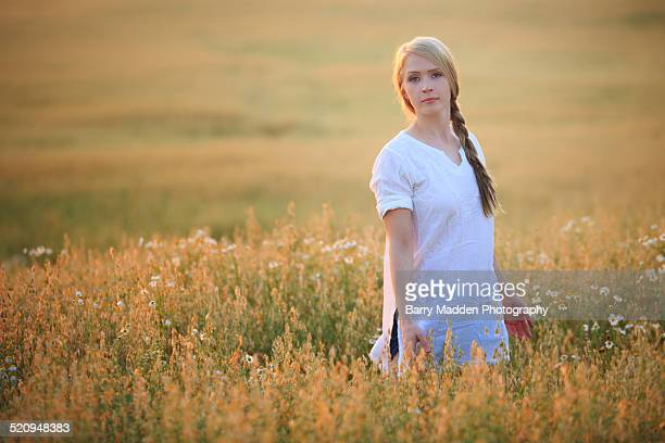 Woman standing in a field at sunset