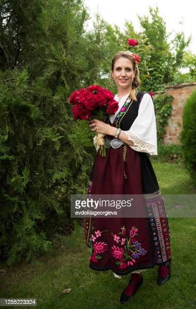 woman standing in a garden wearing a traditional bulgarian costume, bulgaria - 東ヨーロッパ ストックフォトと画像
