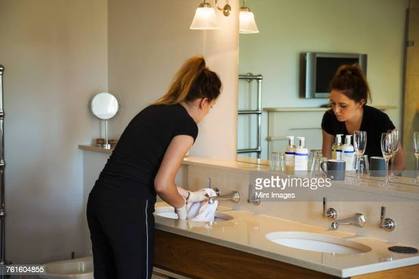 Woman standing in a hotel bathroom in front of mirror, cleaning sink.