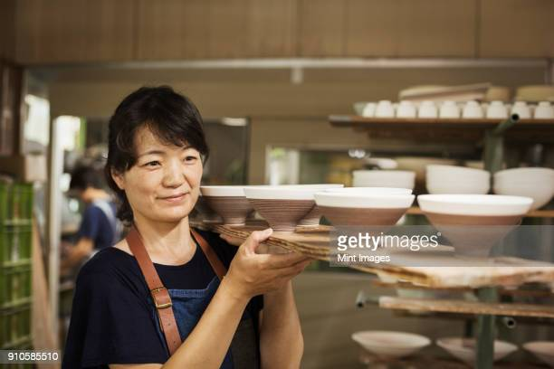 Woman standing in a Japanese porcelain workshop, carrying long wooden tray with bowls.