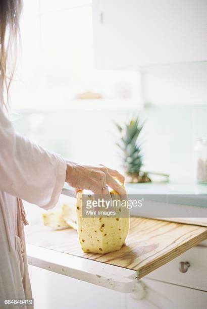 Woman standing in a kitchen, cutting a fresh pineapple.
