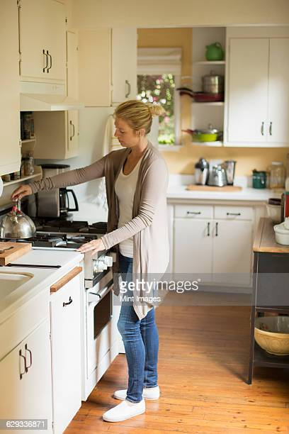 Woman standing in a kitchen, placing a kettle on a stove.
