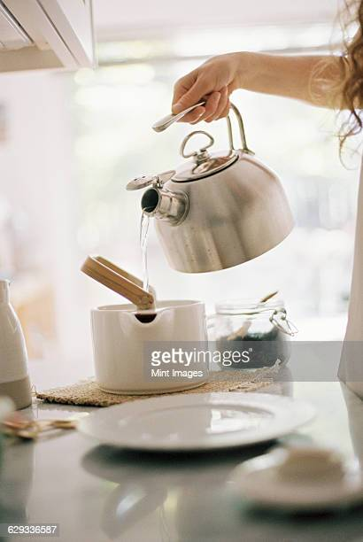 Woman standing in a kitchen pouring hot water from a kettle into a tea pot.