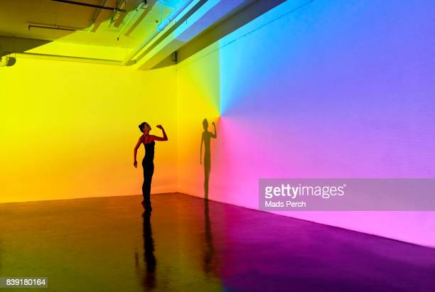 woman standing in a large studio space - yellow stock pictures, royalty-free photos & images