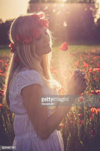 Woman standing in a poppy field at back light