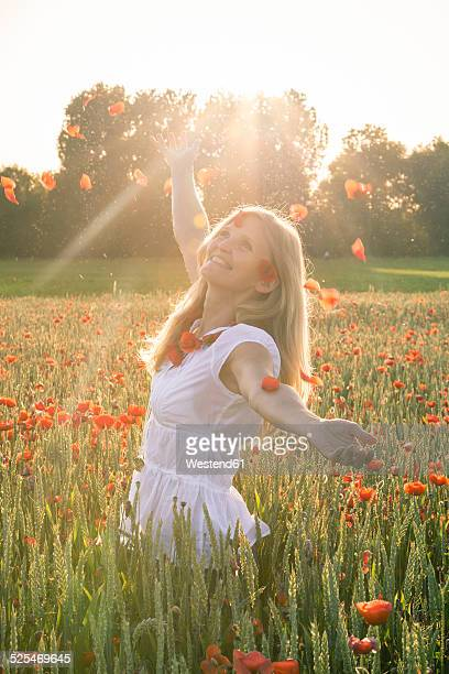 Woman standing in a poppy field throwing petals into the air